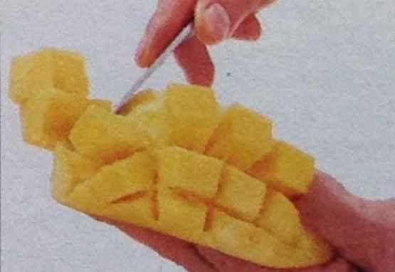 Holding the mango flesh upwards